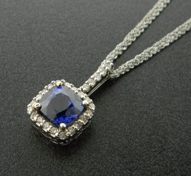 vibrant cushion blue sapphire with a halo of diamonds