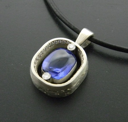 6.58 carat cabochon blue sapphire accented with brilliant cut diamonds. Designed by Rick Little.