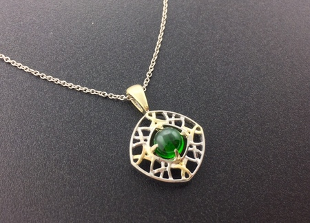 Cabochon cut tsavorite garnet fashioned in 14 karat white and yellow gold. Designed by Rick Little
