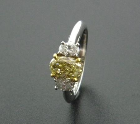 Platinum and 18 karat yellow gold ring with a 1.40 carat fancy yellow oval brilliant cut diamond.