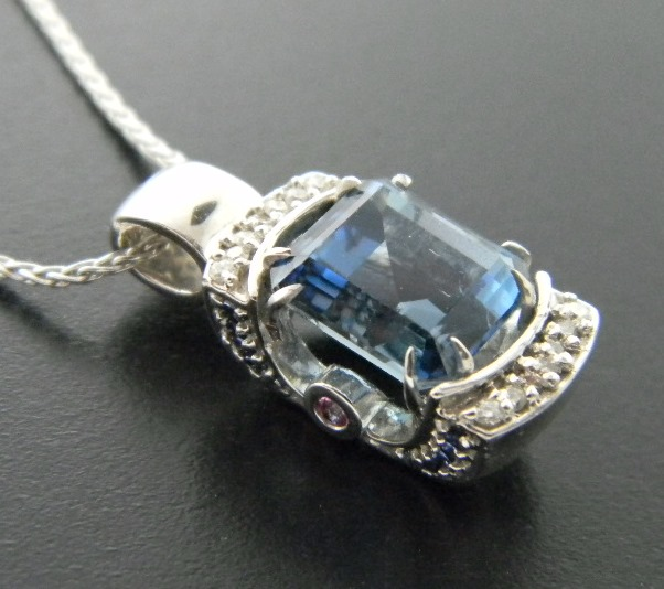 Rare deep blue aquamarine pendant adorned with brilliant cut diamonds, blue and pink sapphires. Designed by Rick Little. : Aspen Originals : Aspen Jewelry Designs