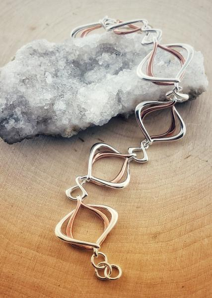 Sterling silver and rose gold overlay entwined bracelet. $210.00