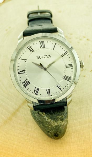 Classic Bulova with a stainless steel case with a silver-white sunray dial, second hand, and black leather strap.