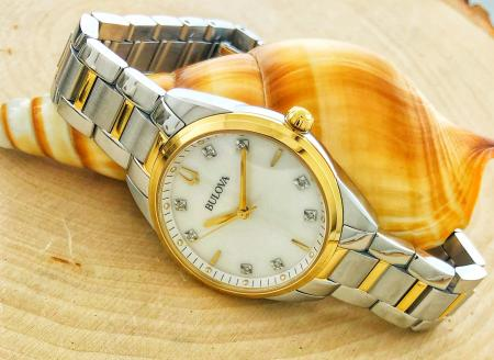 Ladies Bulova with a gold tone and stainless steel case, mother of pearl dial and diamond hour markers.