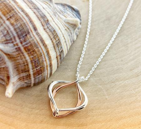 Sterling silver and rose gold overlay entwined necklace. $100.00